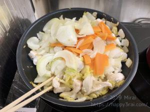 白菜と鶏肉に加熱済みの人参と玉ねぎを加えて炒める様子