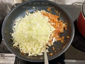玉ねぎとにんじんとトマトジュースにキャベツを加えてを炒める様子