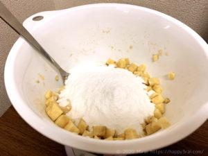 ラカントと塩を加えた角切りさつまいもに米粉を入れる様子
